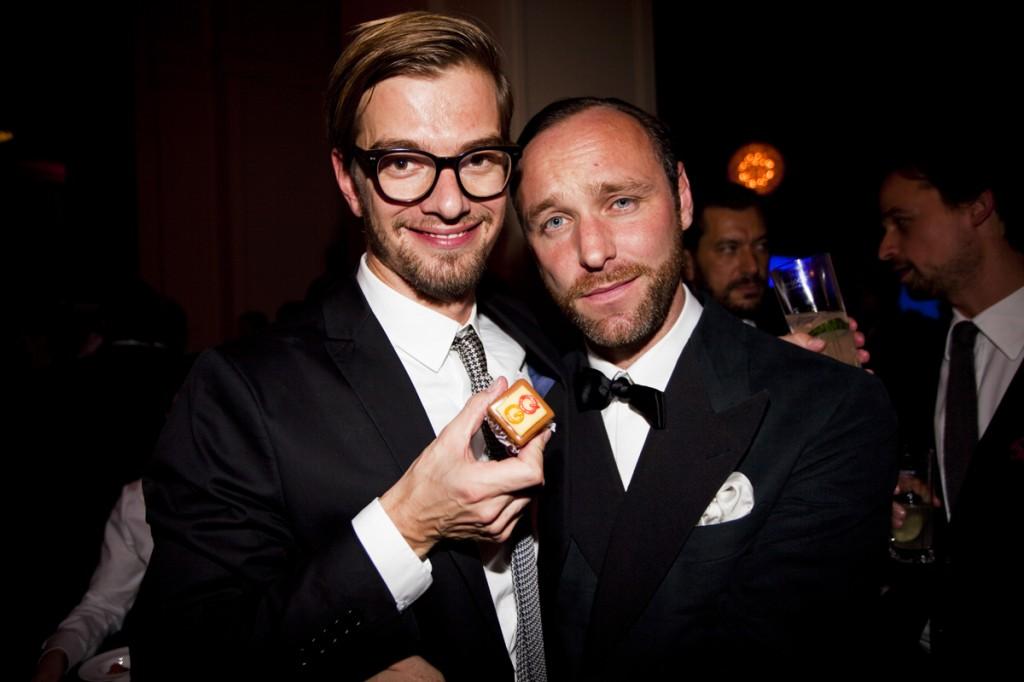 """Joko Winterscheidt (links mit einem Freund) erhielt den Award """"Mann des Jahres"""" zusammen mit Partner Klaas in der Kategorie Fernsehen und freut sich sichtlich über die hausgemachte Praline,"""